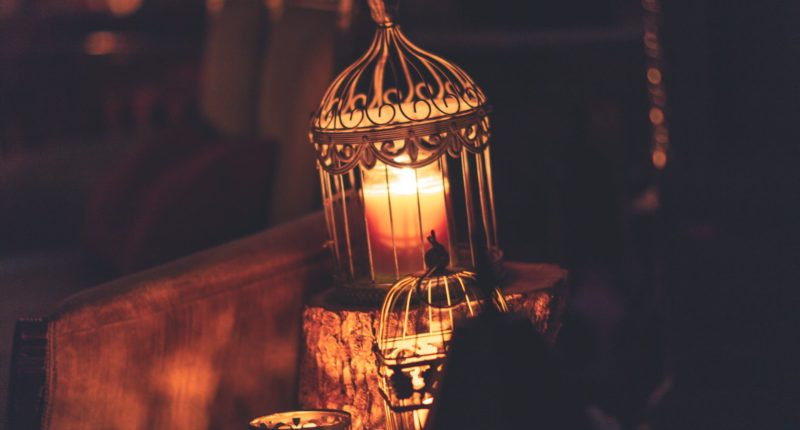 photo of brown metal cage with lighted candle