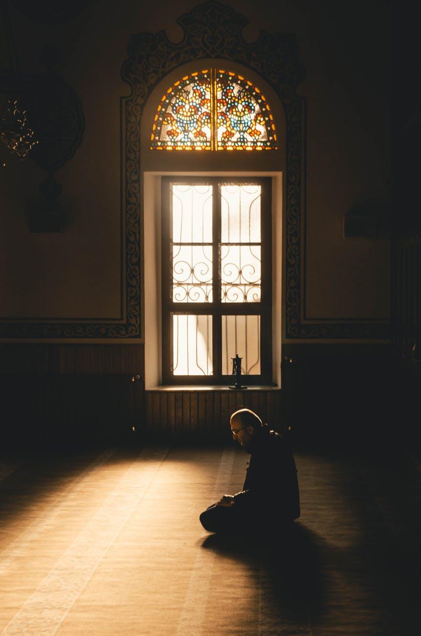 photo of man kneeling while praying