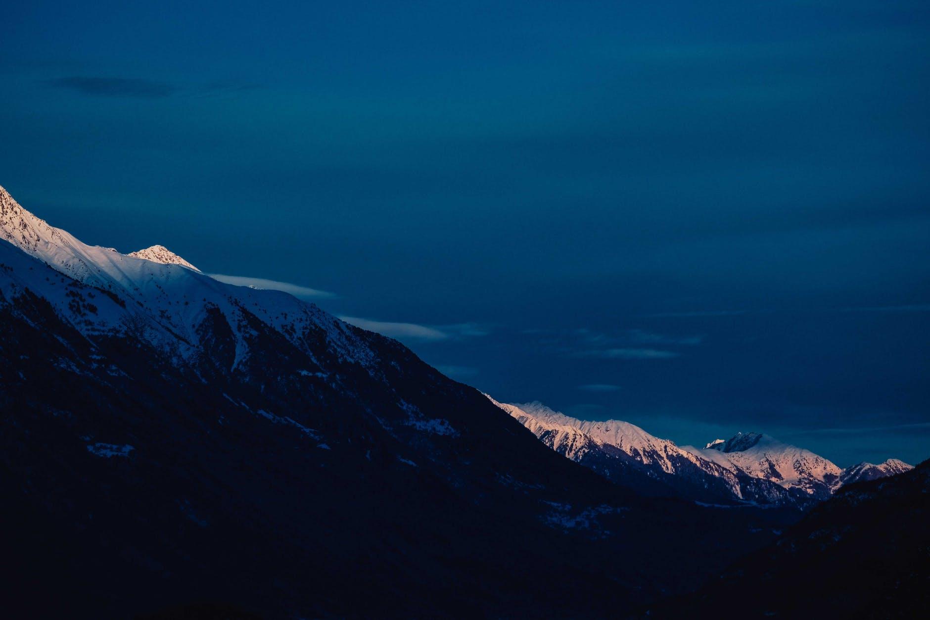 snowy mountainous valley under bright blue sky