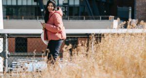 happy ethnic woman using smartphone on street